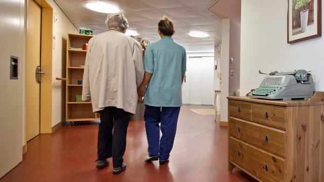 Eine Pflegeperson betreut einen Demenzkranken. Sie gehen Hand in Hand, fotografiert von hinten.