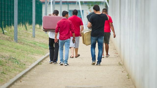 Fünf männliche Flüchtlinge laufen mit Koffern die Strasse entlang.