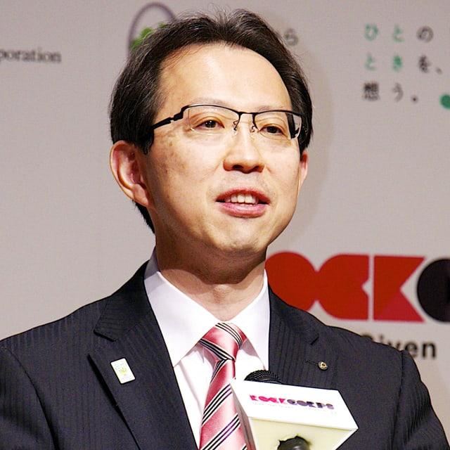 Uchibori mit Anzug und Krawatte spricht in ein Mikrofon.