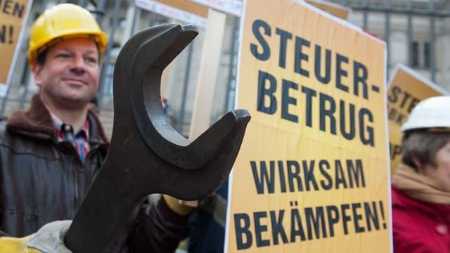 Demonstranten mit einem Plakat und einem grossen Werkzeug.