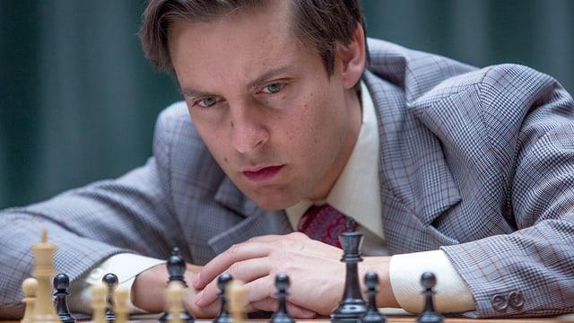 Ein Mann in weissem Hemd und hellblauem Jackett beugt sich konzentriert über ein Schachbrett.