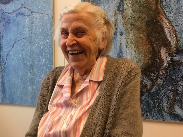 Eine ältere, lachende Frau vor einem Gemälde in Blautönen.