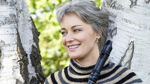 Frau mit Blockflöte steht vor einer Birke.