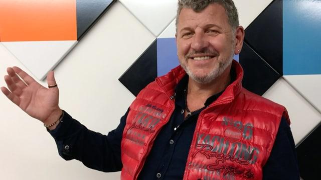 Ein Mann mit roter Weste über einem schwarzen Pullover.