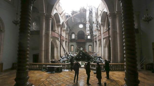 In einem Kirchenraum. Das Dach ist zerstört.