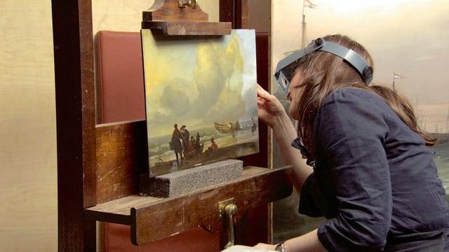 Eine Restauratorin beugt sich über ein Gemälde. Sie trägt eine spezielle Brille.