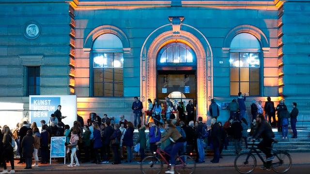 Das beleuchtete Kunstmuseum Bern bei Nacht, davor eine Menschentraube