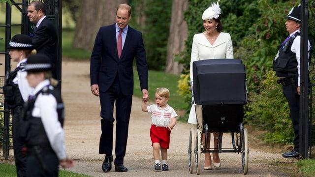 Prinz George geht an der Hand von Prinz William. Neben ihnen schiebt Kate einen Kinderwagen.