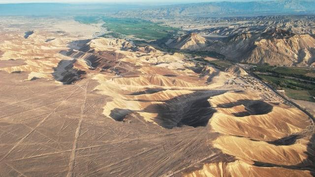 Aus der Vogelperspektive: Hügel und Wüste, darauf grosse geometrische Dreiecke