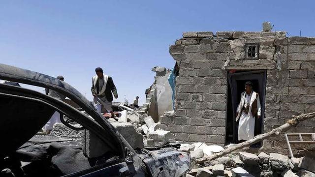 Ein zerstörtes Haus und ein ausgebranntes Auto in Saana.