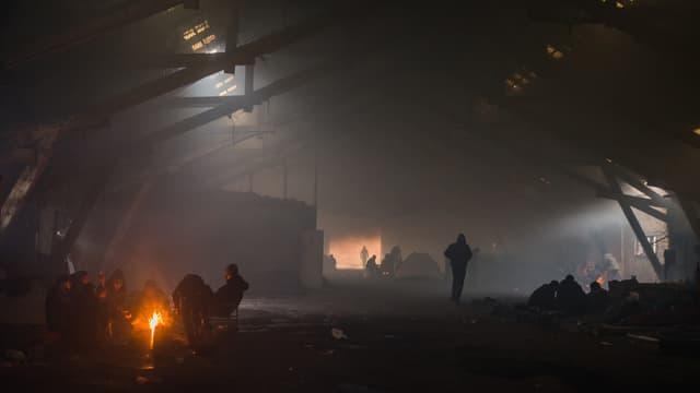 Blick in eine dunkle Lagerhalle, vorne links brennt ein Feuer. Männer sitzen darum herum.