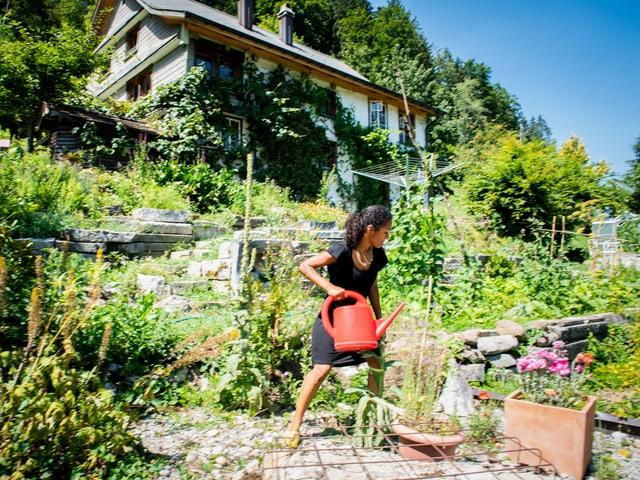 Eine Frau mit langen schwarzen Haaren in schwarzem Kleid steht vor einem Bauernhaus mit grossem Garten und giesst mit einer roten Spritzkanne Pflanzen.