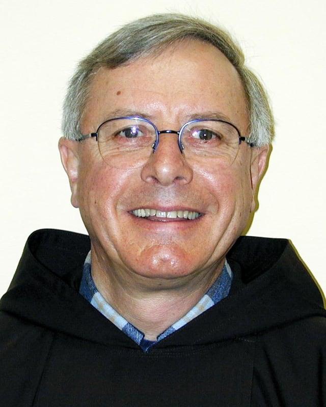 Ein Mann mit Brille und kurzen grauen Haaren lächelt in die Kamera.