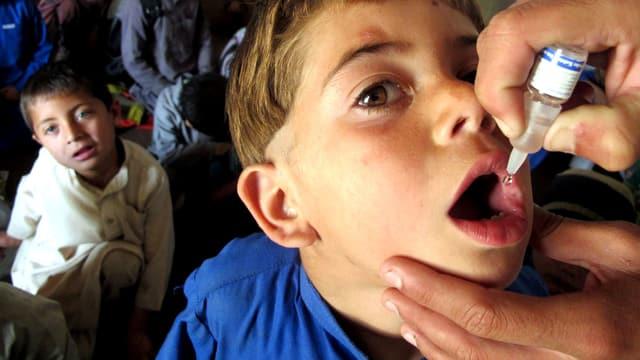 Ein Junge in Pakistan wird mit Tropfen geimpft.