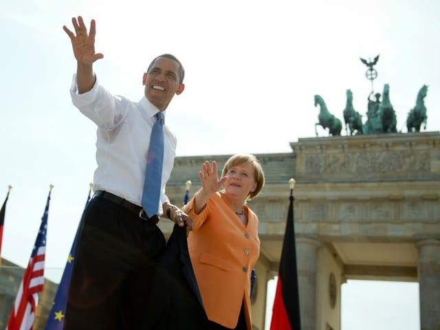Obama hält Merkel bei der Hand, sie stehen vor dem Brandenburger Tor.
