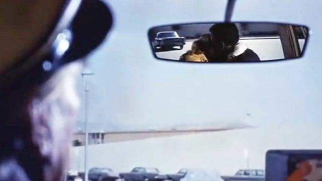 Taxifahrer sieht im Spiegel wie ein Pärchen knutscht.