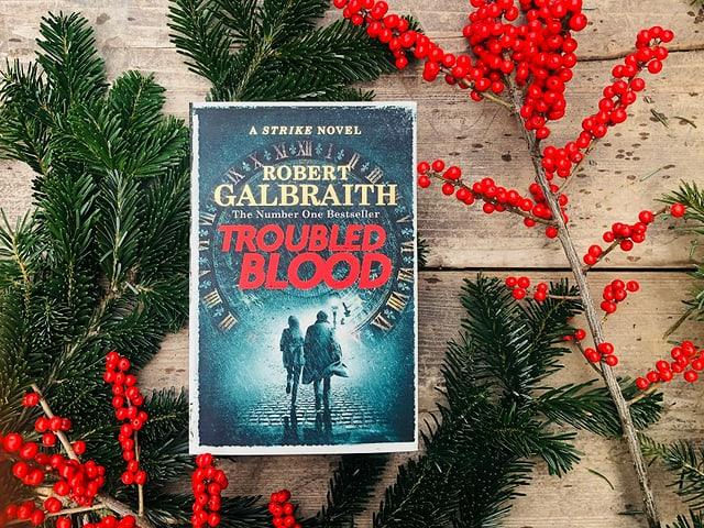 «Troubled Blood» von Robert Galbraith liegt auf Weihnachtsdekoration