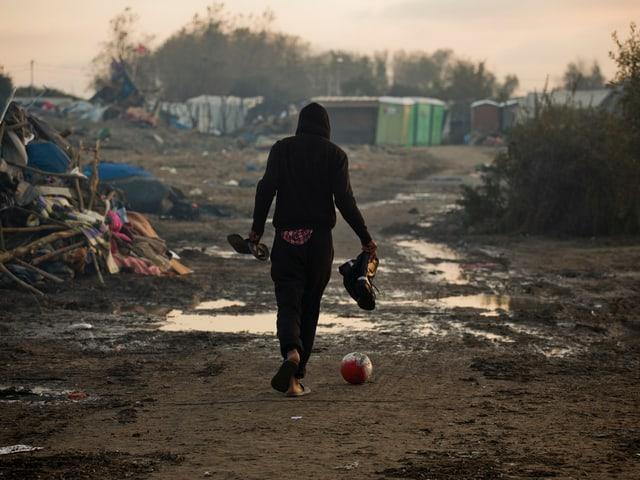 Migrant kickt einen Fussball im Lager von Calais (Ende 2016).