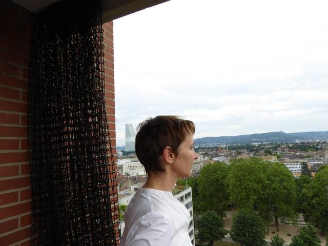 Christine Binswanger steht auf einer Terrasse von Herzog & de Meuronhoch über Basel und schaut in die Ferne.