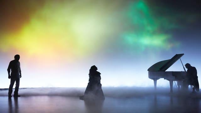 Ein Mann, eine Frau und ein Pianist im gelben und grünen Nebel.