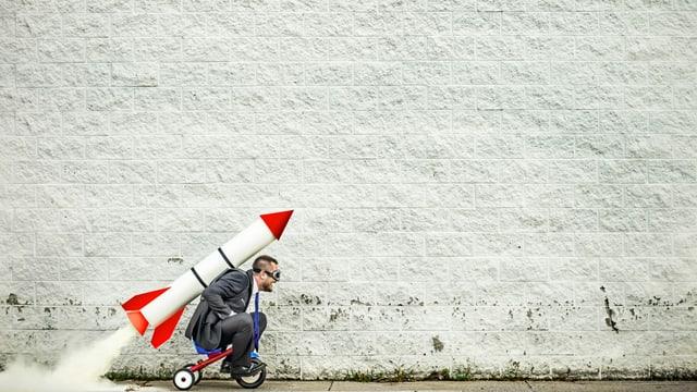 Mann auf Dreirad mit Rakete auf dem Rücken
