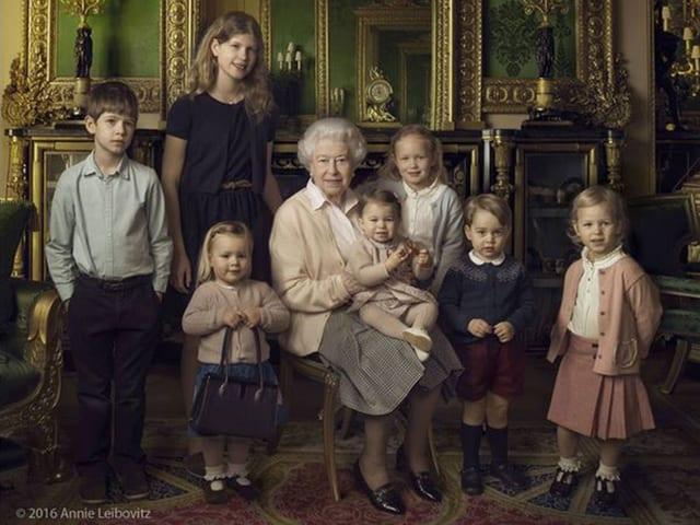 Die Queen sitzt auf einem Stuhl. Um sie herum ihre Grossenkel und zwei ihrer Enkel.