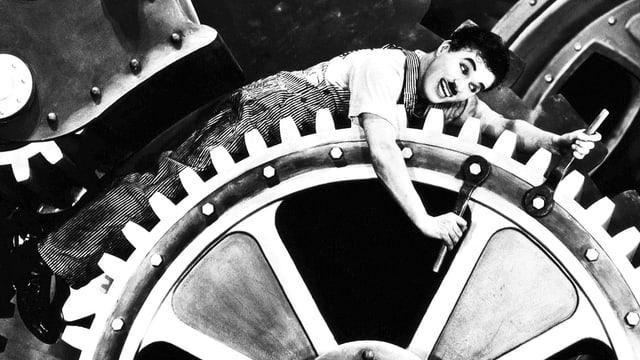 Charlie Chaplin in Zahnrädern feststeckend. Aus dem Film «Modern Times».