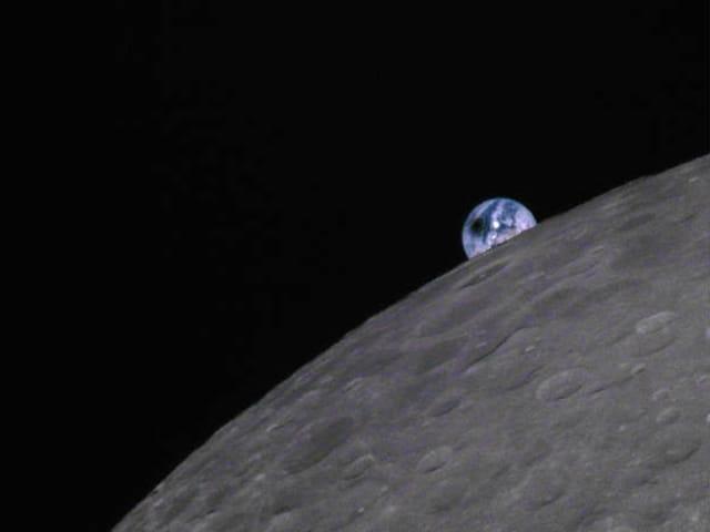 Die Erde geht über dem Mond auf
