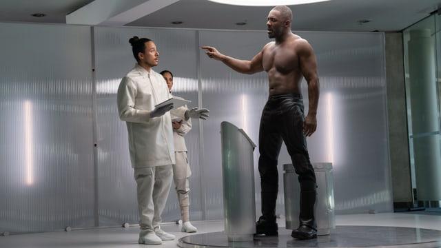 Der Bösewicht Brixton oben ohne und zwei weissbekleidete Personen, die neben ihm Stehen.