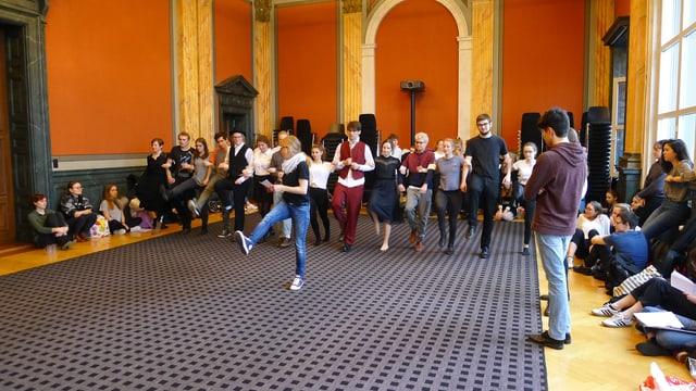 Szene bei einer Theaterprobe mit vielen Jugendlichen in einem alten Festsaal.