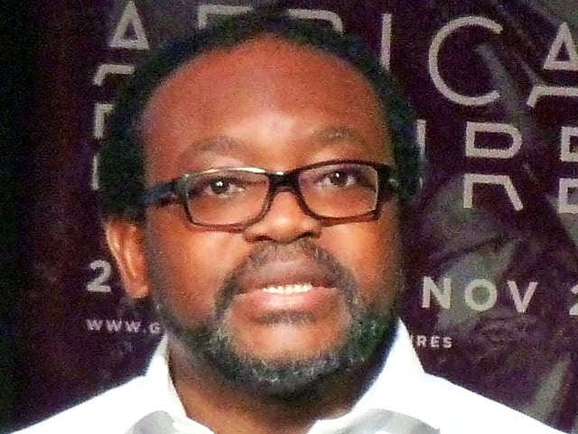 Ein schwarzer Mann mit schwarzer Brille und Bart referiert.