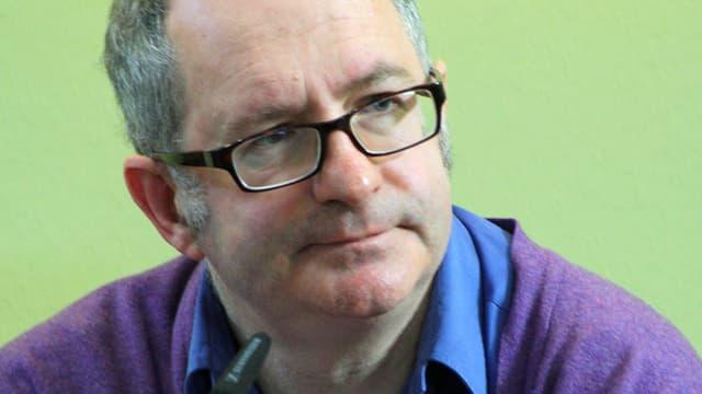 Ein Mann mit Brille vor grünem Hintergrund.