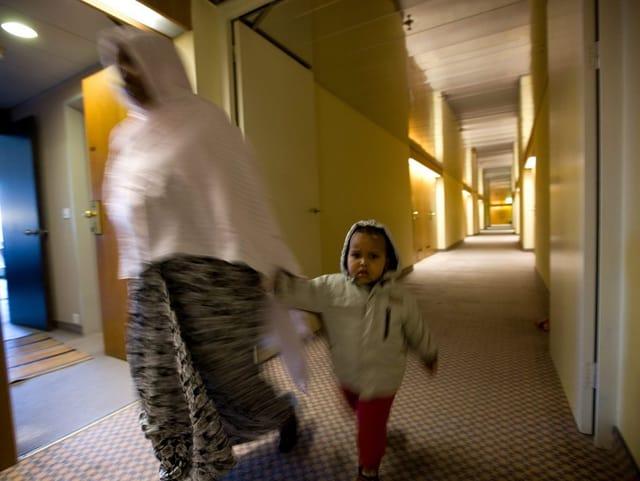 Flüchtlingsfrau mit Kind geht über einen Hausflur.