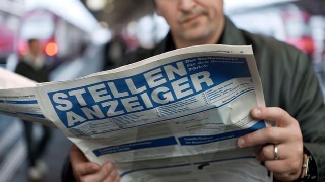 Ein Mann liest den Stellenanzeiger
