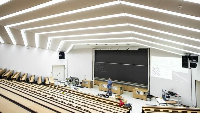 Gähnende Leere im Vorlesungssal, vor der Wandtafel steht einsam ein Dozent.