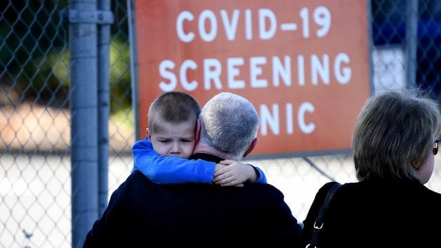 Mann mit Kind vor Schild: Covid-19-Screening-Center