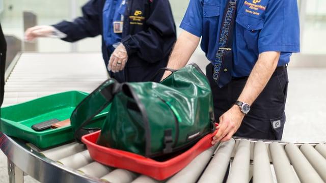 Polizisten kontrollieren Handgepäck am Flughafen.