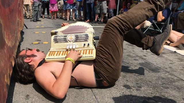 Ein am Boden liegender Mann mit nacktem Oberkörper spielt Akkordeon