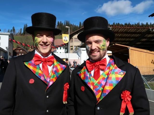 Zwei Männer in farbigen Anzügen.
