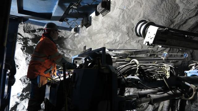 Eine Felsbohrmaschine die von einem Maschinisten in Leuchtkleidung gefahren wird.