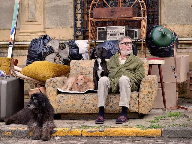 Ein Mann sitzt mit Hunden auf einem Sofa auf einer Strasse.