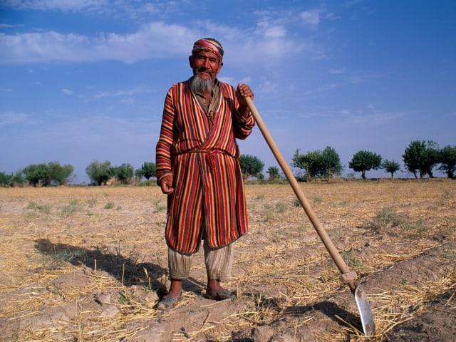 Ein Feldarbeiter im Süden Usbekistans posiert mit einer Schaufel.