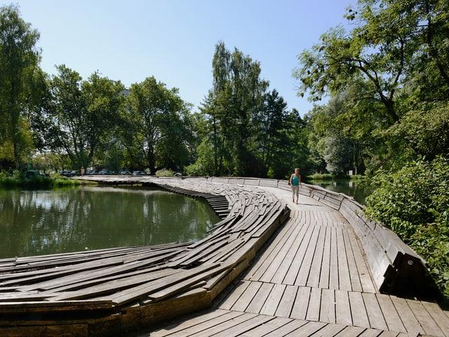 Ein Damm über den Zellweger-Weiher, der aus Holzdielen gebaut ist.