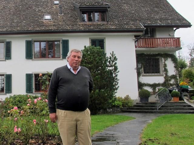 Mann steht im Garten vor einer Villa.