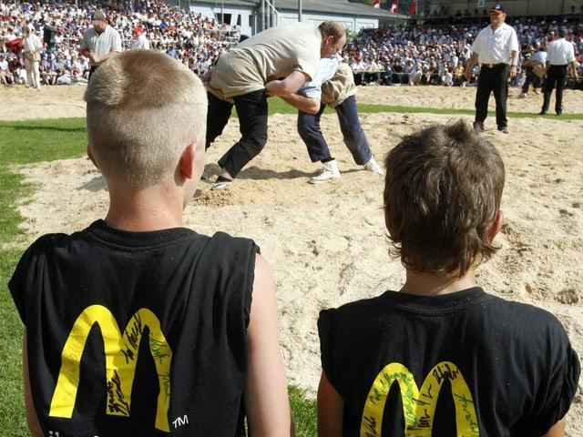 Kinder an einem Schwingfest – sie tragen Shirts mit Werbeaufschrift auf dem Rücken.