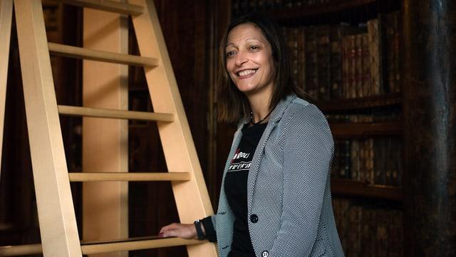 Eine Frau steht vor einer Leiter in einer Bibliothek