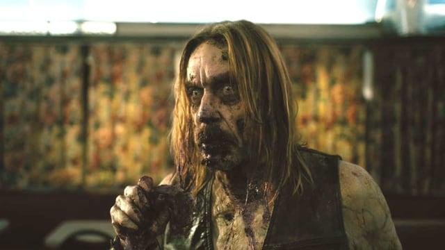 Ein Zombie mit langen Haaren starrt gedankenlos in die Ferne.