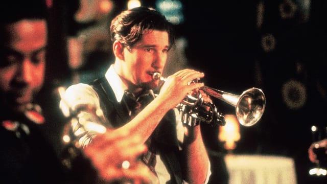 Richard Gere spielt im hochgekrempelten Hemd Trompete.