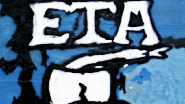 """Graffiti mit dem weissen Schriftzug""""ETA"""" und einem Beil auf einer blauen Wand."""