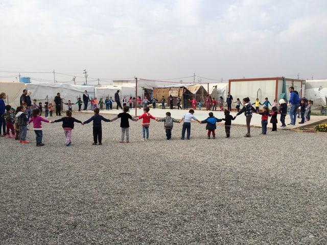 Kinder und Erwachsene die sich an den Händen halten, bilden einen grossen Kreis.